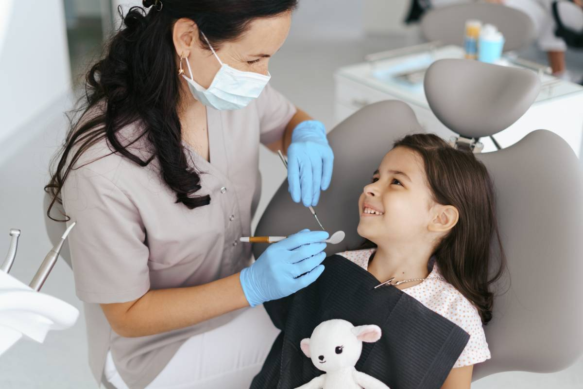 child in dental chair smiling at dentist, holding stuffed animal