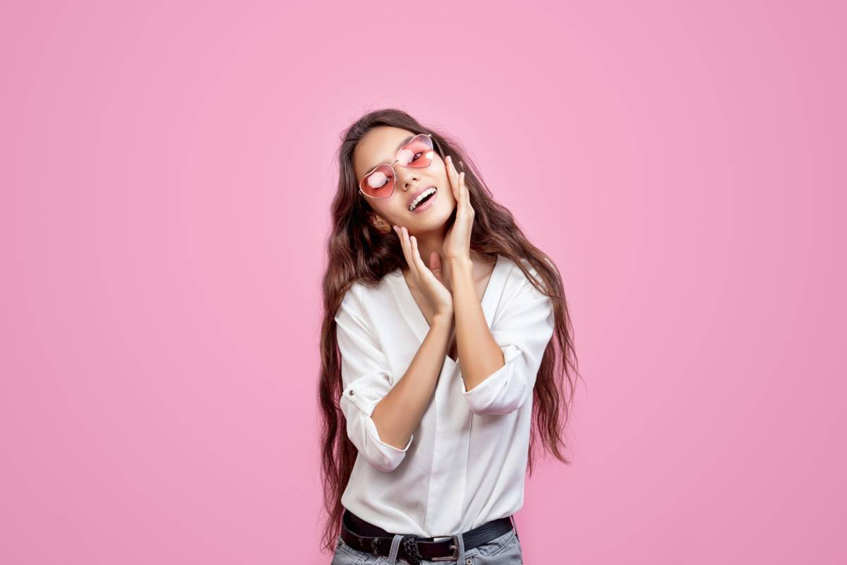 woman smiling against pink background with pink glasses