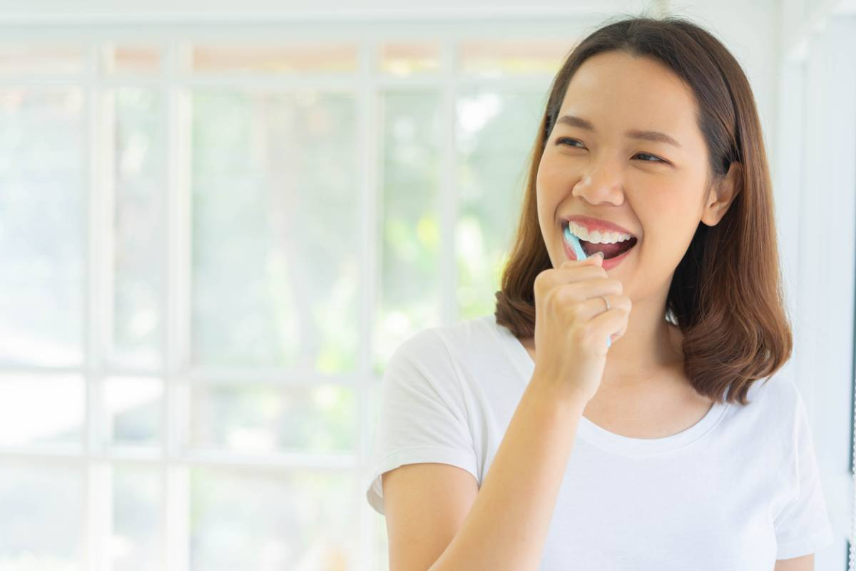 Woman brushing her teeth using the best technique for her gums.