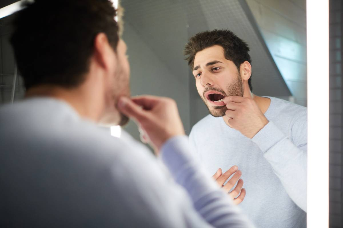 man checking for early signs of gum disease